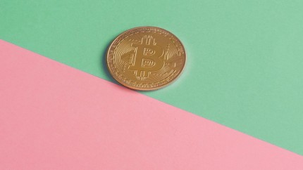 Bitcoin coin on green pink background